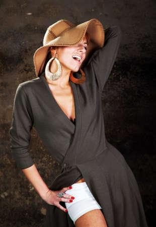 Een jonge vrouw in een strooien hoed met een betonnen muur Stockfoto