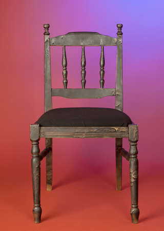 old-fashioned dark wood chair against red wall
