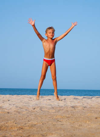 The boy jumps up on the sandy beach near the sea Stock Photo - 16247278