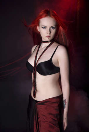 A beautiful woman with red hair and a black bra photo