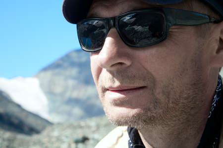 The man in the mountains in sunglasses photo