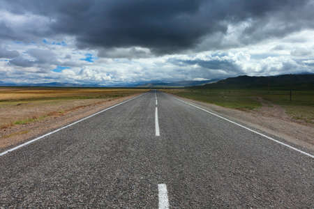 desert storm: An empty desert road with dark and foreboding storm clouds on the horizon.