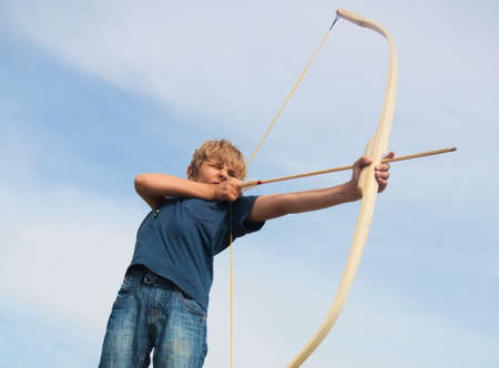 Boy shoots a bow at a target, in the open air Stock Photo