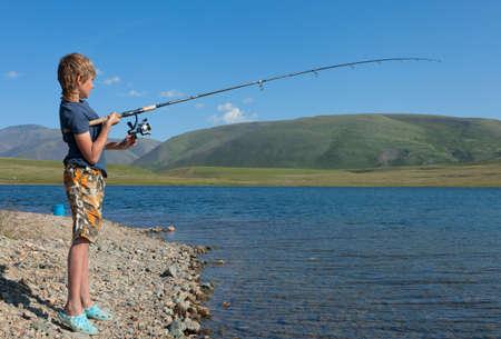 grayling: El muchacho con un grayling captura de hilado. Pescados hermosos en lagos de monta�a y r�os