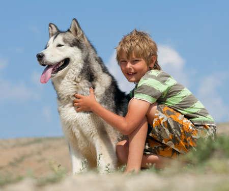 Boy hugging a fluffy dog. Husky dog breed