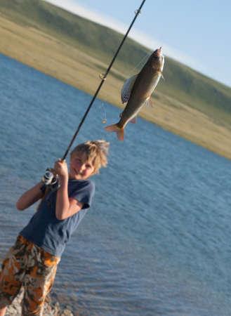 grayling: El muchacho con una captura hilado t�malo pescado hermosa en lagos de monta�a y r�os