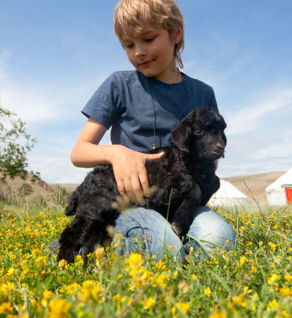 Boy on her lap a little black goat Stock Photo