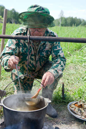 A man prepares the fishing catch in a pot on the fire photo