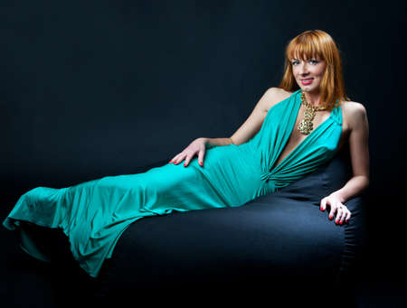 Woman in evening dress reclining on a chair on black background photo