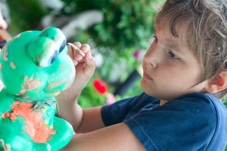 Boy painting with a brush, a green ceramic frog