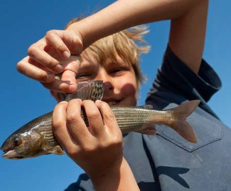 Boy caught grayling Stock Photo - 19031662