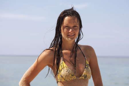Young beautiful woman in a yellow bikini on the beach photo