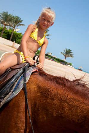 Children riding on horseback on the beach photo