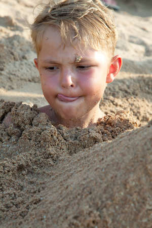the funny boy in sand photo