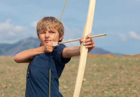 archery target: Boy shoots a bow at a target, in the open air Stock Photo