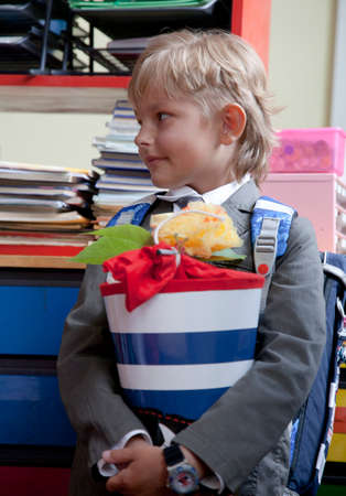 Little school boy with his blue schoolbag and a large cornet of cardboard filled with sweets and little presents given to children on their first day at school. photo