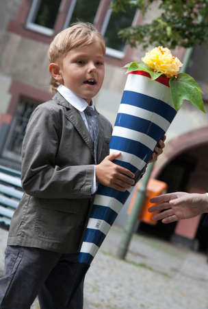 Boy, a first grader for the first time goes to school. Behind his back pack, in the hands of a package of sweets. This is Berlin photo