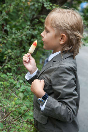 boy in a gray suit eats ice cream in the park photo