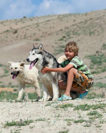 Boy hugging a fluffy dog. Husky dog breed photo