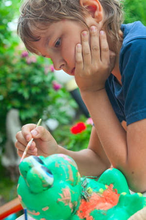 Boy painting with a brush, a green ceramic frog photo