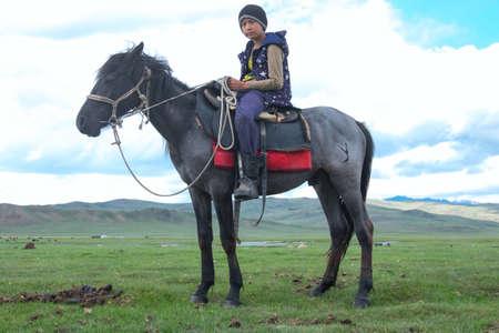 Asian boy riding a Mongolian horse