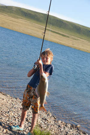The boy with a spinning catch grayling. Beautiful fish in mountain lakes and rivers
