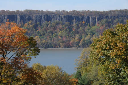 The Palisades overlooking the Hudson River with autumnal trees in the foreground