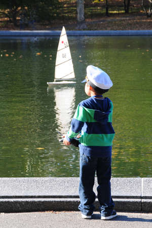 remote controls: Boy wearing a sailor cap remote controls his model yacht.