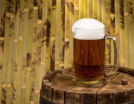 amber: beer glass of beer on a wooden barrel