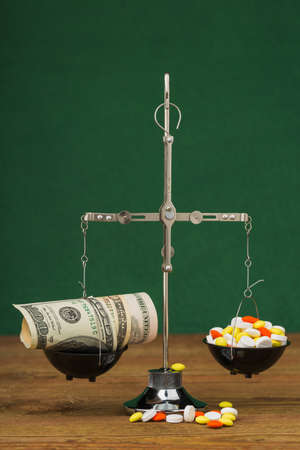legitimacy: scales, money and a lot of colored pills Stock Photo