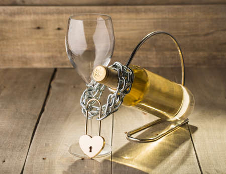 shackled: Bottle of white wine and a glass shackled love chain with a lock.