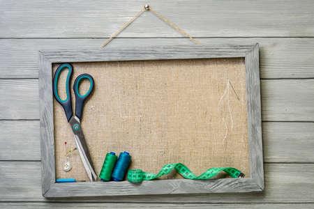 coser: Marco en el fondo de madera y artículos para coser.