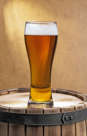smudged: beer glass of beer on a wooden barrel