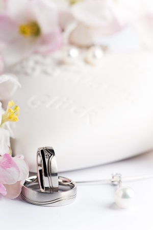 two wedding rings with earrings and flowers in the background