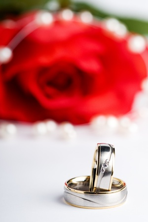 two wedding rings with a necklace and a red rose in the back Stock Photo