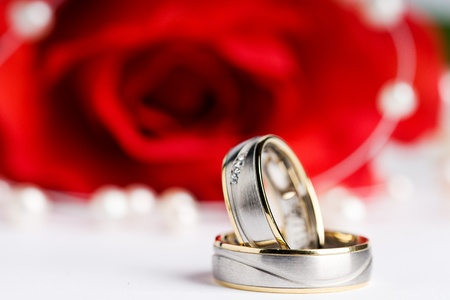 exempted: two wedding rings with a necklace and a red rose in the back Stock Photo