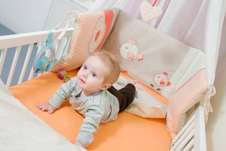 baby lying in the latticed bedsted and plays photo