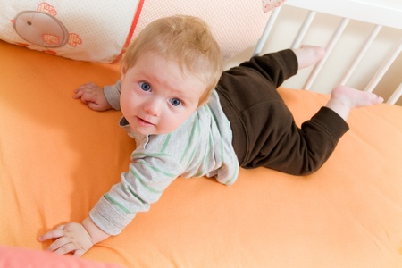 latticed: baby lying in the latticed bedsted and plays Stock Photo