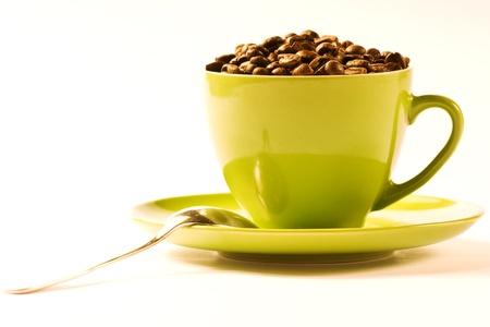green cup of coffee with brown beans on white ground