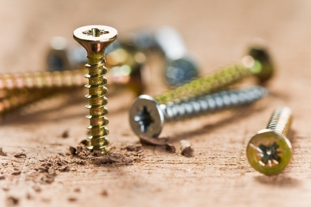Wood work: screws screwed in wood with wood shavings Stock Photo