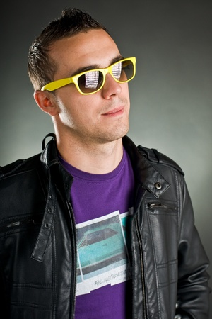 attractive man with yellow sunglasses and leather jacket photo