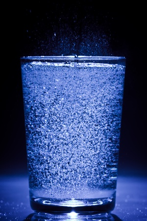 blue glass filled with soda water on white ground