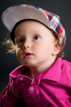 casual boy with cap in studio on gray ground photo