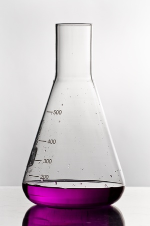 violett: chemistry glass with toxic violett liquid on white ground