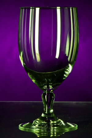 violett: glass of water in yellow and green gleam with violett background