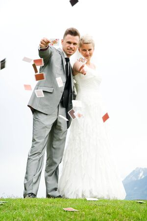 dress suit: bride and groom couple throuing play cards