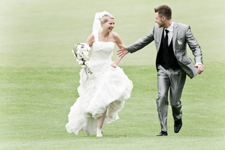 married couples: bride and groom running on the green grass