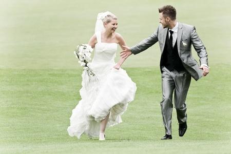 bruid en bruidegom lopen op het groene gras