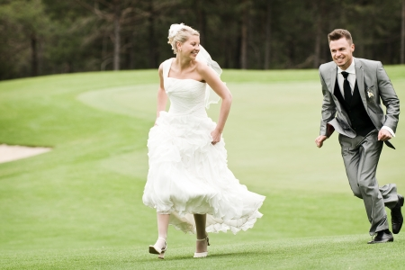 bride and groom running on the green grass photo