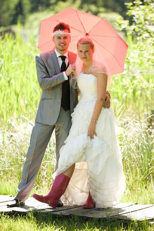 weddingrings: bride and groom with red gumboots and umbrella in the nature